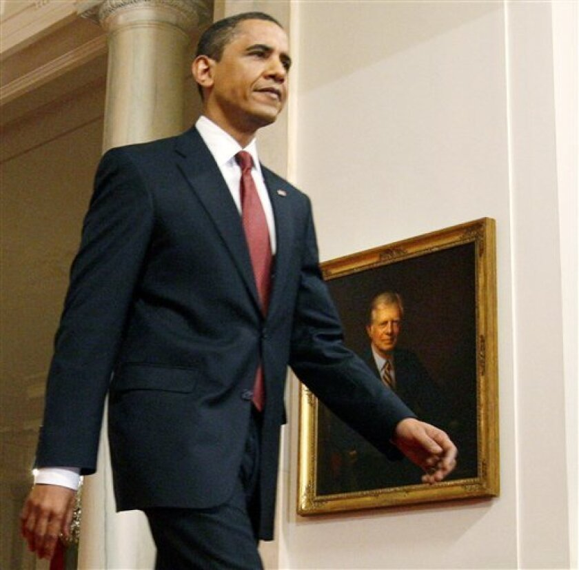FILE- In this March 24, 2009 file photo, President Barack Obama walks past a portrait of former President Jimmy Carter before speaking at a news conference Tuesday, March 24, 2009, in Washington. Carter has some advice for Barack Obama as he gears up for the 2012 election: Don't alienate voters with controversial positions. The Georgia Democrat told The Associated Press on Tuesday that just about everything he did alienated voters, from sealing a treaty to hand over the Panama Canal to establishing diplomatic ties with China. (AP Photo/Charles Dharapak, File)