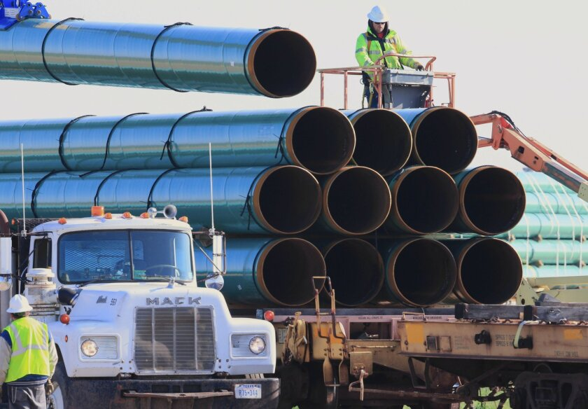 FILE - In this May 9, 2015, file photo, workers unload pipes for a proposed oil pipeline that would stretch from the Bakken oil fields in North Dakota to Illinois. On Tuesday, Congress unanimously passed a bill that includes provisions for pipeline safety across the country. (AP Photo/Nati Harnik, File)