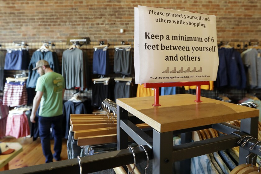 A sign reminding customers of social distancing is posted in the Bink's Outfitters store Wednesday in Murfreesboro, Tenn.