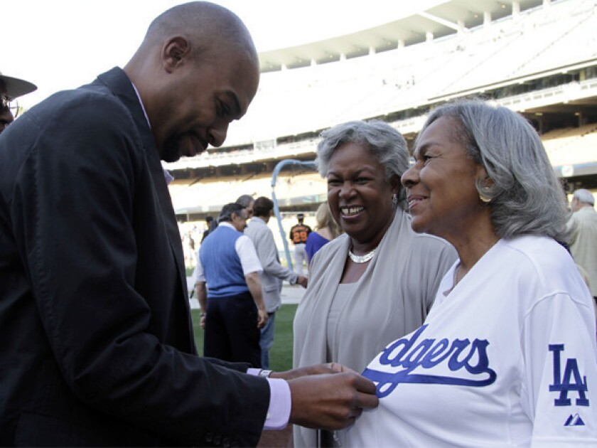 Sharon Robinson looks on as her son, Jesse, helps Rachel Robinson, Jackie¿s widow, with a jersey at Dodger Stadium in May. Sharon will join the Dodgers' board of directors before next season.