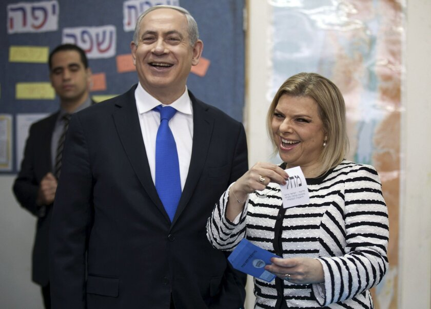 FILE - In this Jan. 22, 2013 file photo, Israeli Prime Minister Benjamin Netanyahu stands by his wife Sara as she casts her ballot at a polling station in Jerusalem. Israeli media reported Sunday, May 29, 2016 that a police investigation has recommended indicting the wife of Prime Minister Benjamin