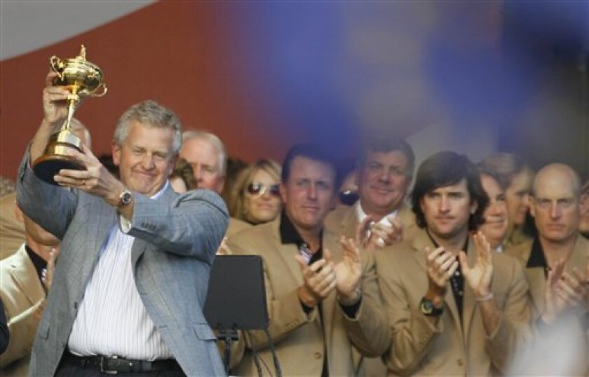 The U.S. team members look on as Europe team captain Colin Montgomerie lifts the trophy after winning the 2010 Ryder Cup golf tournament at the Celtic Manor Resort in Newport, Wales, Monday, Oct. 4, 2010. (AP Photo/Alastair Grant)