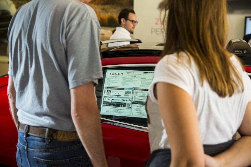 People check out a Tesla Model S inside the electric carmaker's Santa Monica showroom. California's electric vehicle rebate program could be in danger of running out if lawmakers and the governor don't sign off on a plan to spend cap-and-trade funds soon.