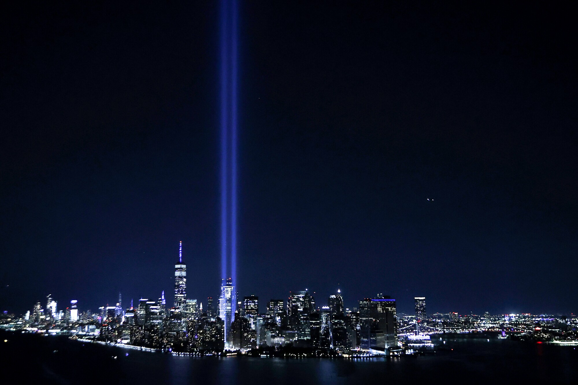 The Tribute in Light showing two columns of light reaching into the night sky shines up from the Manhattan skyline.