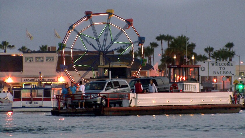 The Ferris wheel at the Balboa Fun Zone is lit up behind one of the ferries shuttling cars and pedestrians.