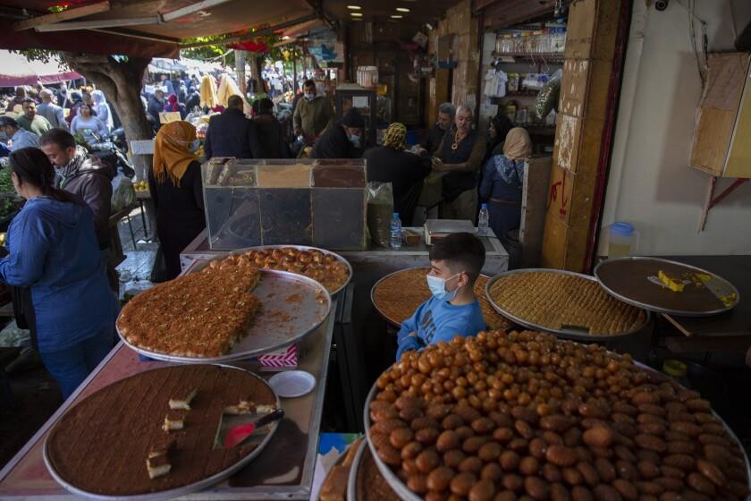 سینی های گرد بزرگ و پر از دسر میزهای بازار شلوغ را می پوشاند.