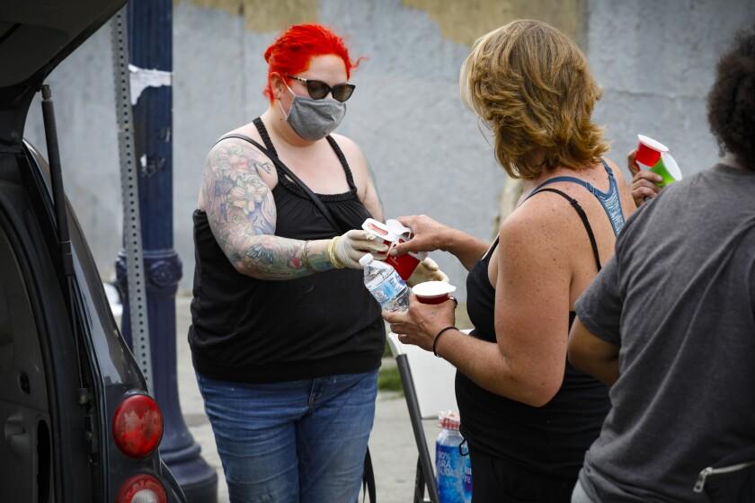 Chelsea Muniz, a la izquierda, reparte comida a personas sin hogar en Imperial Avenue, cerca de 17th Street