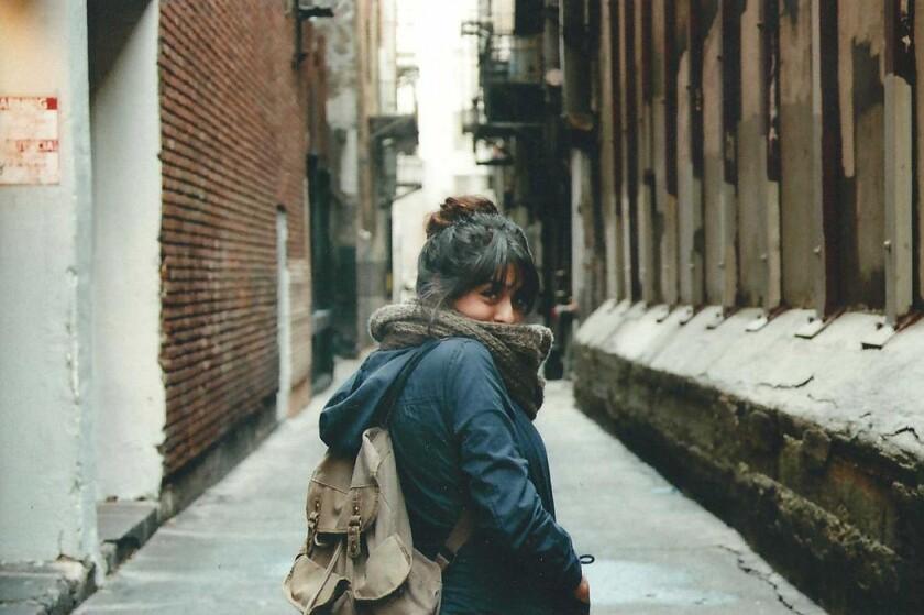 A woman walking down an alleyway glances back toward the camera.