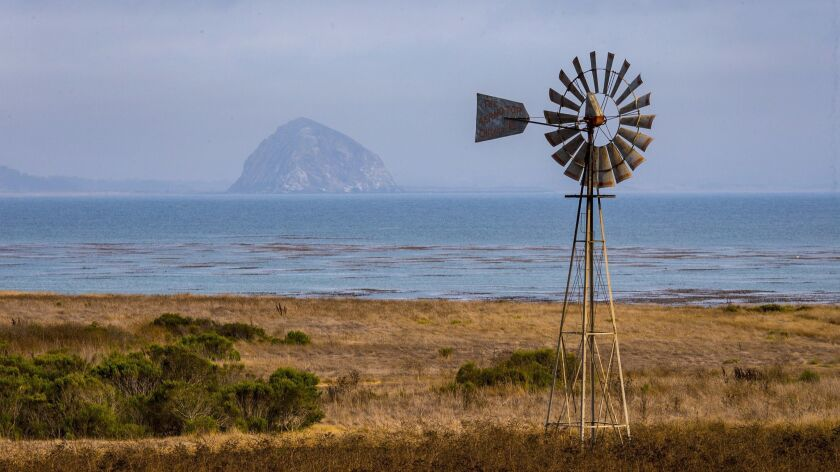 MORRO BAY, CA -- WEDNESDAY, AUGUST 3, 2016: A windmill lines an undeveloped stretch of coast along