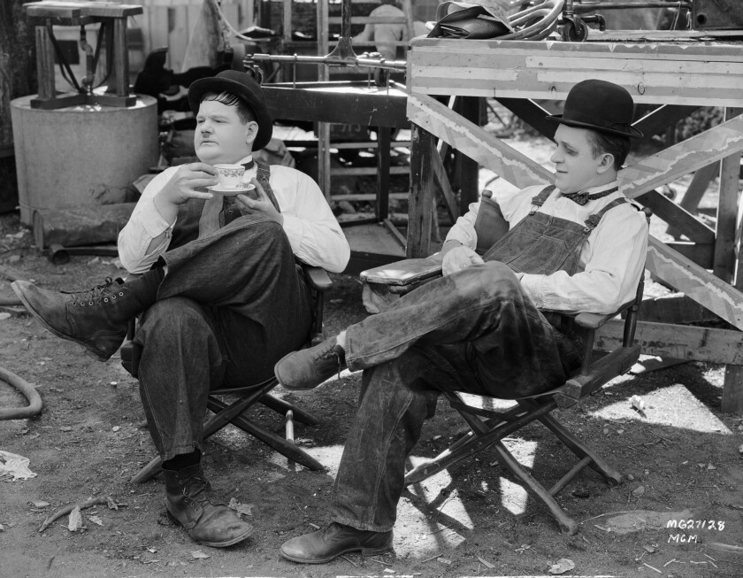 """Oliver Hardy, left, and Stan Laurel during a break in the filming of """"Towed in a Hole."""""""