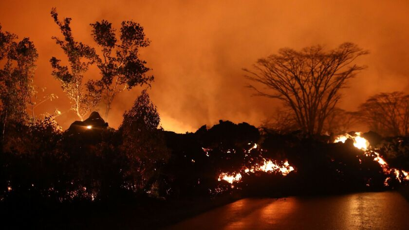 Lava from a Kilauea volcano fissure advances on a roadway in Leilani Estates, on Hawaii's Big Island, on Friday. Such images aren't helping the tourism industry.