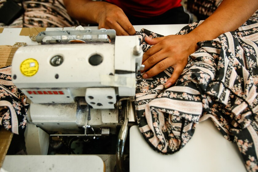 A person operates a sewing machine