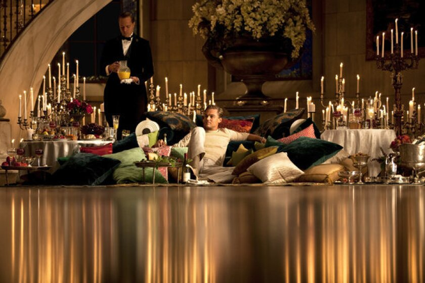 """Nouveau riche Jay Gatsby (Leonard DiCaprio) stages a picnic on the floor of his ballroom. """"We brought in a garden bench and filled it and the floor with velvet, satin and silk pillows,"""" production designer Catherine Martin said. The urn of cascading orchids was inspired by Constance Spry, a famed British florist to the royals in the early 20th century."""