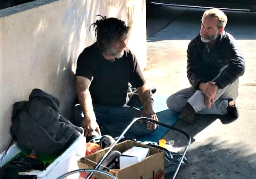 Dr. Jonathan Sherin, director of the Los Angeles County Department of Mental Health, counsels a man who is homeless in Hollywood in October 2019.