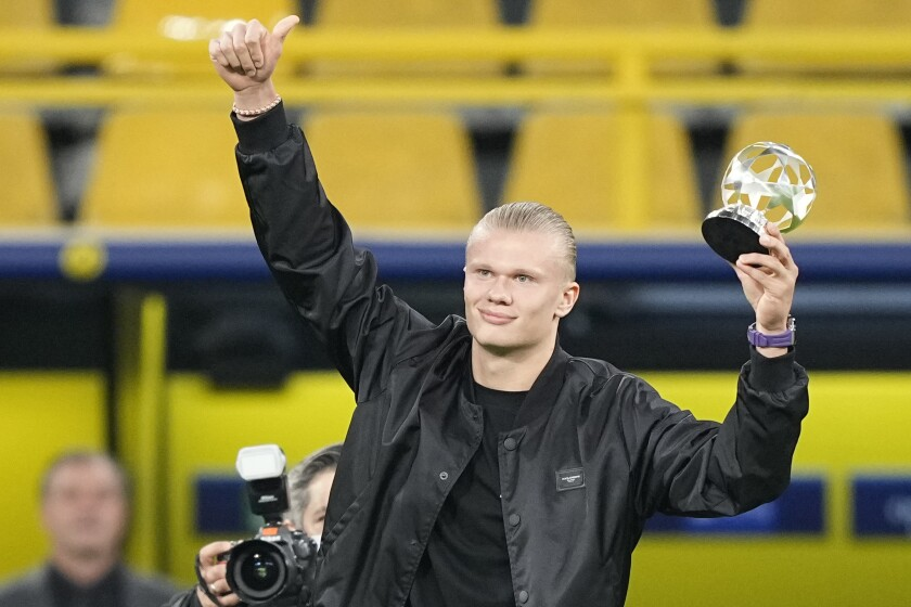 Dortmund's Erling Haaland celebrates with the UEFA award for the best forward ahead of the Champions League Group C soccer match between Borussia Dortmund and Sporting CP Lisbon, in Dortmund, Germany, Tuesday, Sept. 28, 2021. (AP Photo/Martin Meissner)