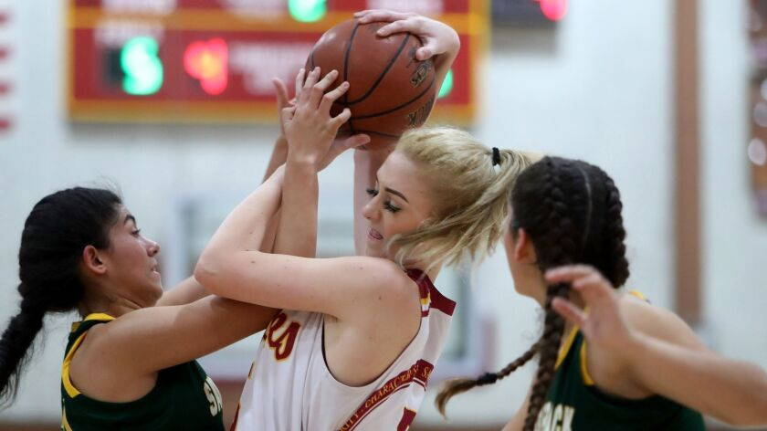 Ocean View High School girls' basketball player Helen Reynolds battles for the ball in the Premier