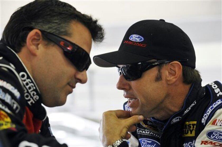 Tony Stewart, left, and Matt Kenseth talk in the garage during practice for Sunday's NASCAR Sprint Cup Series auto race at Atlanta Motor Speedway, Friday, Aug. 31, 2012, in Hampton, Ga. (AP Photo/Rainier Ehrhardt)