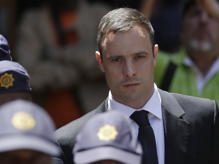 FILE - In this Friday, Oct. 17, 2014 file photo, Oscar Pistorius is escorted by police officers as he leaves the high court in Pretoria, South Africa. Pistorius' lawyers said Tuesday Feb. 27, 2015, that they will challenge a court decision to allow prosecutors to take the case to the Supreme Court seeking to convict the Olympic runner of the more serious crime of murder, for shooting girlfriend Reeva Steenkamp in 2013. (AP Photo/Themba Hadebe, FILE)