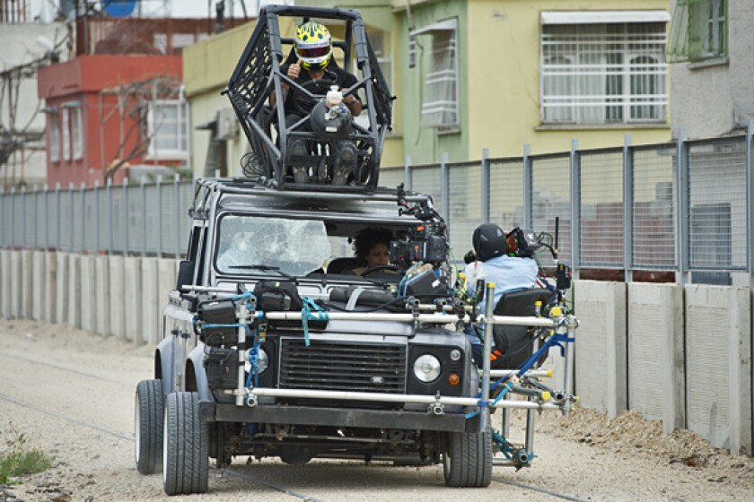 In this photo from the set of 'Skyfall,' stunt driver Ben Collins is seen on the roof of a Land Rover while actress Naomie Harris is filmed inside.
