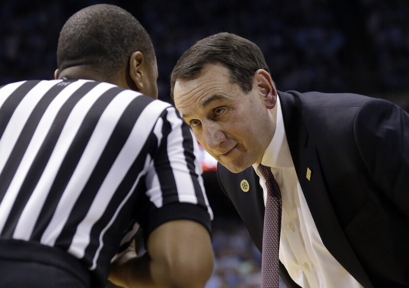 Duke coach Mike Krzyzewski speaks with an official during the second half of the team's NCAA college basketball game against North Carolina in Chapel Hill, N.C., Wednesday, Feb. 17, 2016. Duke won 74-73. (AP Photo/Gerry Broome)