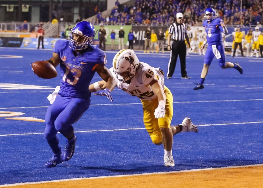 Boise State running back Jeremy McNichols (13) runs the ball for a touchdown past Wyoming linebacker Lucas Wacha (45) during the first half of an NCAA college football game in Boise, Idaho, on Saturday, Oct. 24, 2015. (AP Photo/Otto Kitsinger)