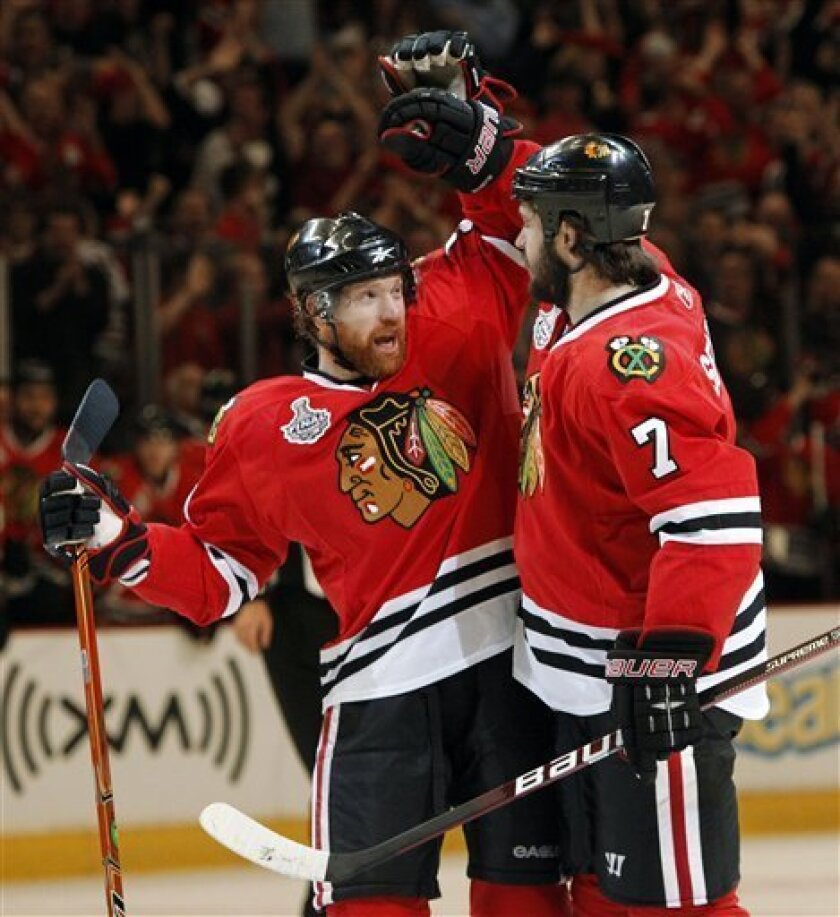 Chicago Blackhawks defenseman Brent Seabrook (7) is congratulated by defenseman Brian Campbell, left, after Seabrook scored against the Philadelphia Flyers in the first period of Game 5 of the NHL Stanley Cup hockey finals on Sunday, June 6, 2010, in Chicago. (AP Photo/Nam Y. Huh)