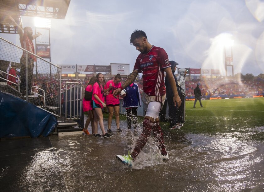 FC Dallas forward Maximiliano Urruti (37) splashes in rain water as he exits the field for a weather delay during the first half of a MLS soccer game on Thursday, June 2, 2016, in Frisco, Texas.  (Ashley Landis/The Dallas Morning News via AP) MANDATORY CREDIT; MAGS OUT; TV OUT; INTERNET USE BY AP M