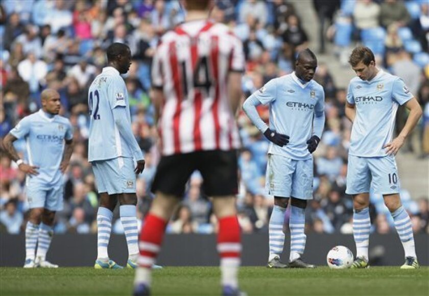 Manchester City's Mario Balotelli, second right, and Edin Dzeko, right, wait for play to restart after Sunderland's second goal during their English Premier League soccer match at The Etihad Stadium, Manchester, England, Saturday, March 31, 2012. (AP Photo/Jon Super)