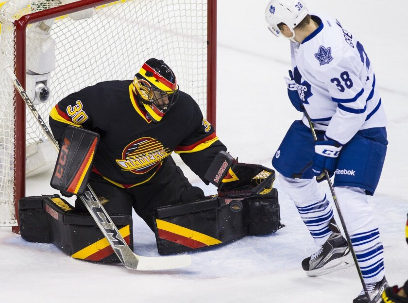 Vancouver Canucks goaltender Ryan Miller (30) makes a save against Toronto Maple Leafs' Colin Greening (38) during second-period NHL hockey game action in Vancouver, British Columbia, Saturday, Feb. 13, 2016. (Ben Nelms/The Canadian Press via AP) MANDATORY CREDIT