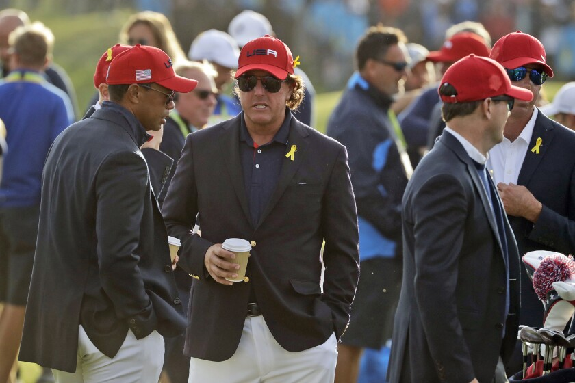 FILE - In this Sept. 30, 2018, file photo, Tiger Woods, left, and Phil Mickelson wait for the closing ceremony after Europe won the Ryder Cup on the final day of the 42nd Ryder Cup at Le Golf National in Saint-Quentin-en-Yvelines, outside Paris, France. Woods will be missng from the upcoming Ryder Cup, while Mickelson will serve as a vice-captain on the team. The pandemic-delayed 2020 Ryder Cup returns the United States next week at Whistling Straits along the Wisconsin shores of Lake Michigan. (AP Photo/Matt Dunha, File)