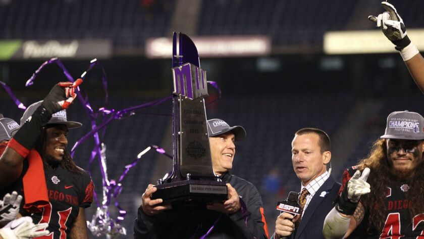 Aztecs coach Rocky Long holds up the Mountain West Conference trophy after SDSU beat Air Force in the title game last year.