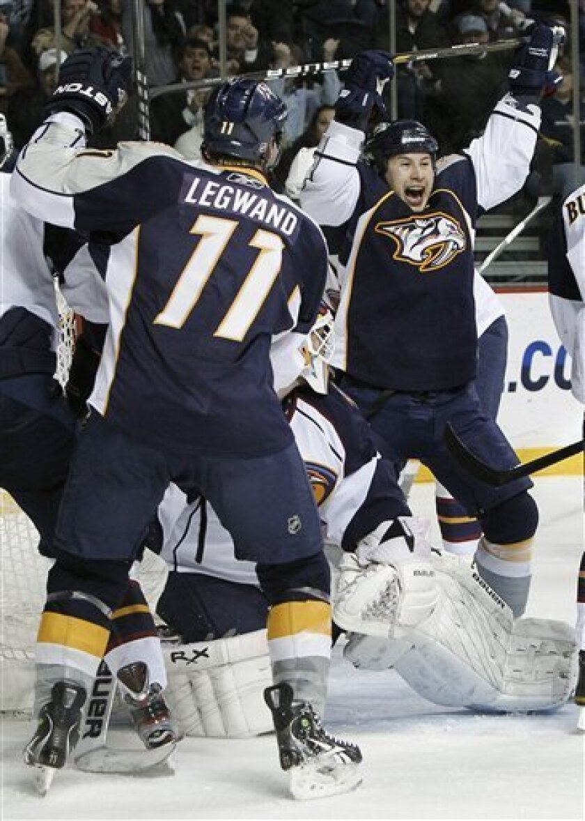 Nashville Predators right wing Jordin Tootoo, right, celebrates after scoring against Atlanta Thrashers goalie Chris Mason, center, in the first period of an NHL hockey game Tuesday, April 5, 2011, in Nashville, Tenn. At left is Predators center David Legwand (11). (AP Photo/Mark Humphrey)