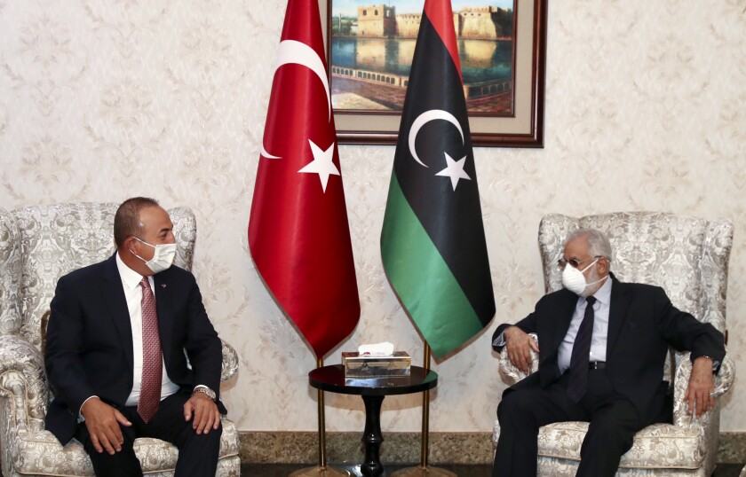 Turkey's Foreign Minister Mevlut Cavusoglu, left, and Muhammed Tahir Siyala, Foreign Minister of Libya's internationally-recognized government, speak during a meeting, in Tripoli, Libya, Wednesday, June 17, 2020.(Fatih Aktas/Turkish Foreign Ministry via AP, Pool)
