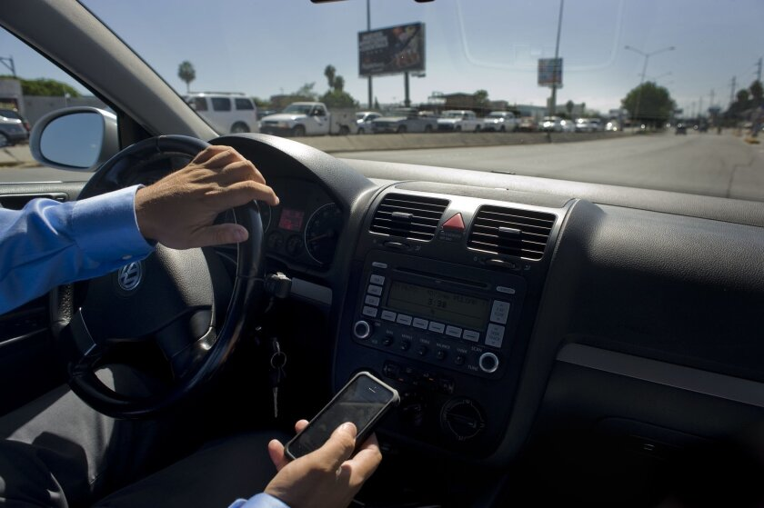 An Uber driver shows his smart phone that he uses to receive clients as he drives in Tijuana's La Mesa district on July 15, 2015 in Tijuana, Mexico..Photo - David Maung.
