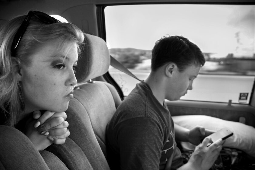 As the family drove to Thousand Oaks for the operation to remove Sam's breast tissue, Sam plays a game on his phone as his sister, Jacq looks down the road.