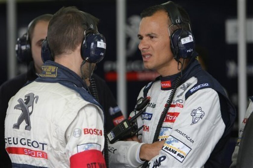 Peugeot 908 No8 french driver Stephane Sarrazin has a talk with mechanics during the qualifying practice session of the 79th 24-hour Le Mans endurance race, in Le Mans, western France, Thursday, June 9, 2011. The race will start on next Saturday, June 11, 2011. (AP Photo/Vincent Michel)