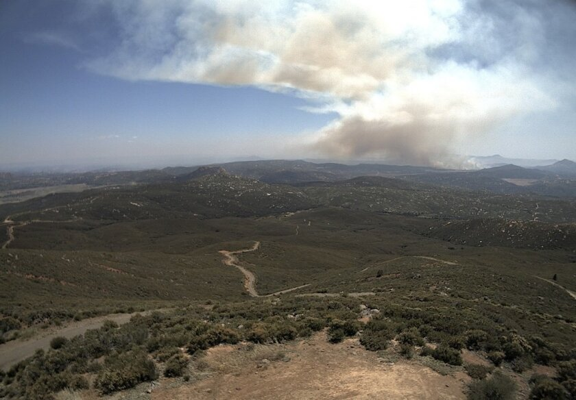 A UC San Diego camera atop Los Pinos Mountain, which is south of Interstate 8 and northeast of the fire, captures smoke rising from the blaze.