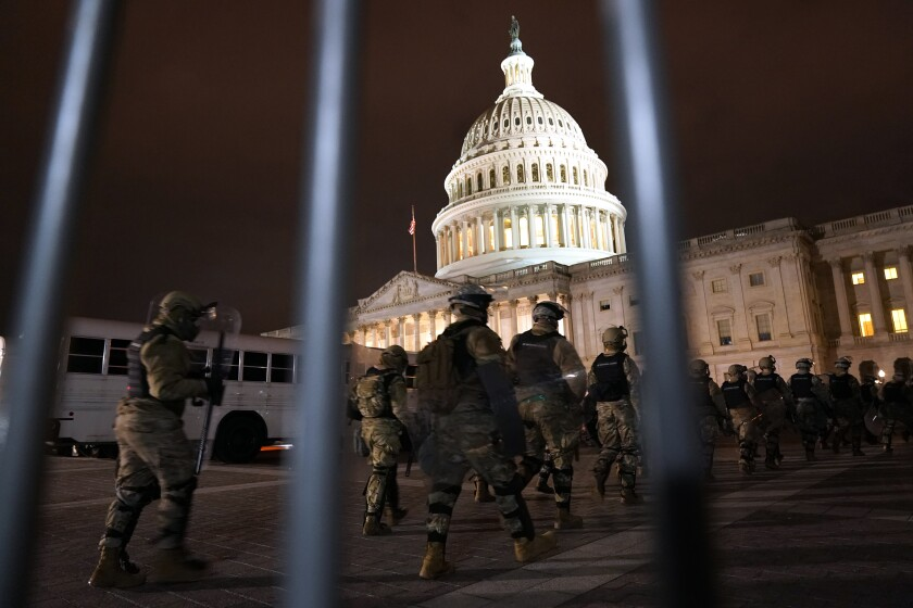 The U.S. Capitol Building is seen through a police barricade as troops march toward the building.