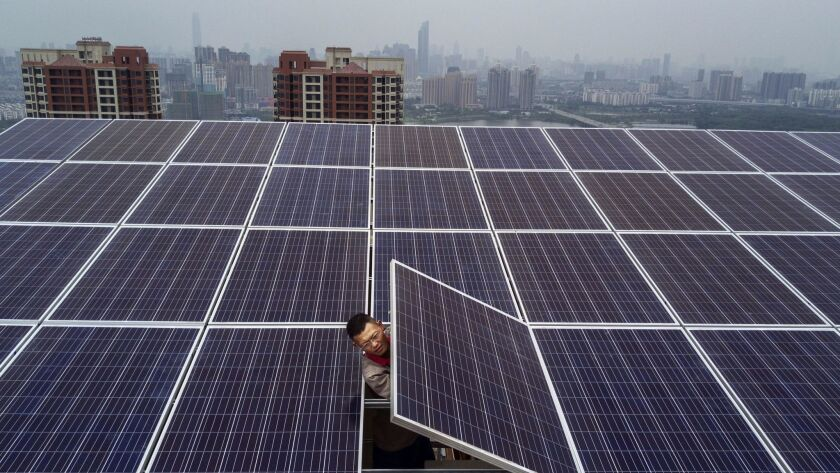 A worker from Wuhan Guangsheng Photovoltaic Co. works on a solar panel project on the roof of a 47-s