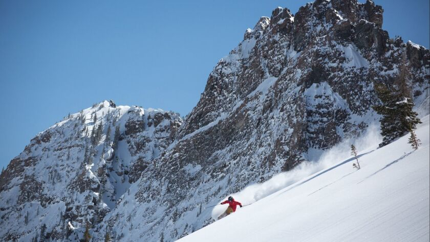 A skier races past the rock formations of Alta's downhill terrain.