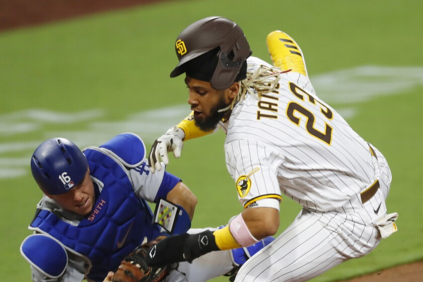 San Diego Padres Fernando Tatis Jr. collides with Los Angeles Dodgers catcher Will Smith at home plate.