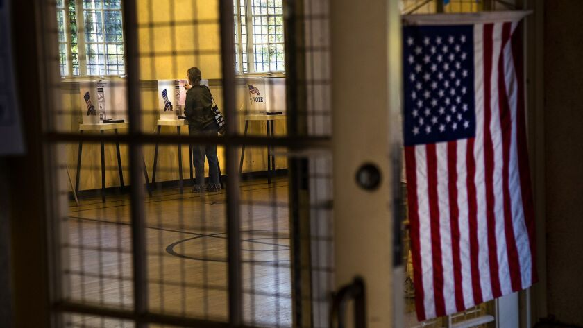 A voter checks her ballot while voting at Silver Lake Recreation Center