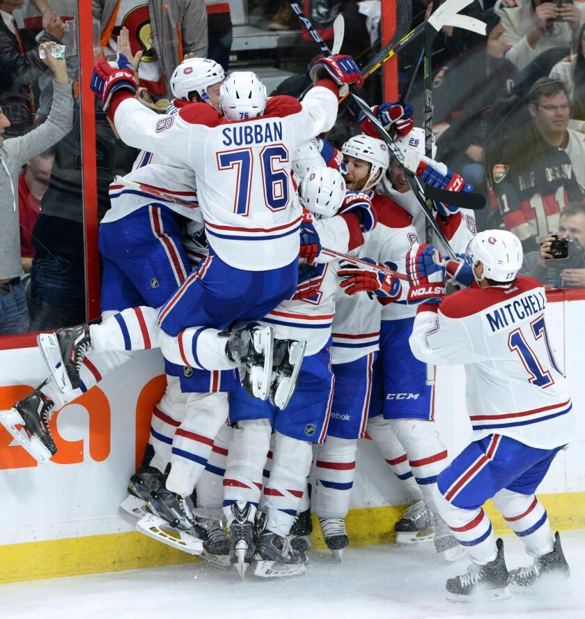 Montreal Canadiens celebrate their 2-1 victory over the Ottawa Senators in sudden death overtime of game 3 of first round Stanley Cup NHL playoff hockey action in Ottawa, Ontario, on Sunday, April 19, 2015.  (Sean Kilpatrick/The Canadian Press via AP)   MANDATORY CREDIT