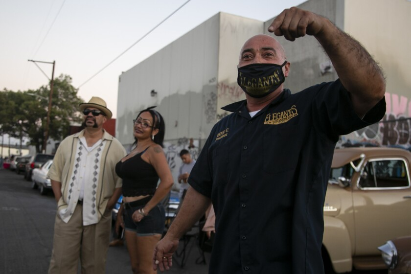 Rene Castellon of the Elegants Montebello car club teases friends from across the street during a gathering in L.A.