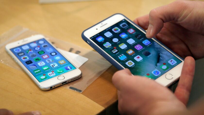 FILE - In this Friday, Sept. 16, 2016, file photo, a customer sets up his new iPhone 7 Plus, right,