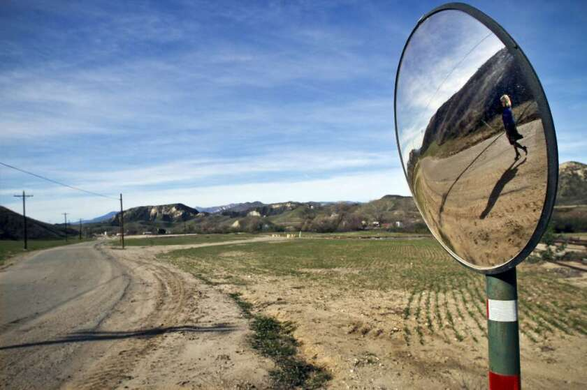 Marlee Lauffer, spokeswoman for Newhall Land and Farming Co., is reflected in a mirror during a tour of Newhall Ranch, the site of a proposed new city 35 miles north of Los Angeles.