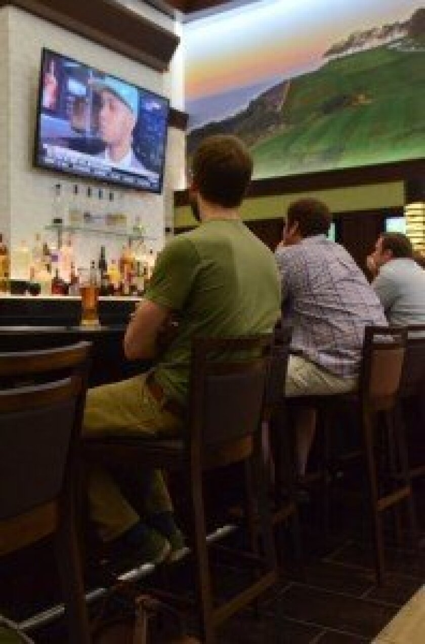 Before catching a flight, patrons can watch one of the restaurant's dozen flat-screen TVs while enjoying brews at the bar.