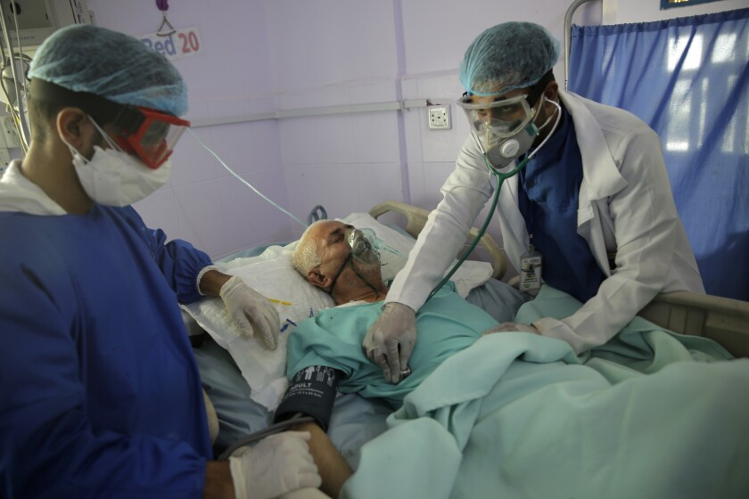Medical workers tend to a COVID-19 patient in an intensive care unit at a hospital in Sana, Yemen.