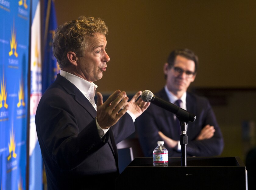 U.S. Sen. Rand Paul (R-Ky.) makes a point on stage as the Libre Initiative's executive director, Daniel Garza, listens during a speech in Las Vegas.