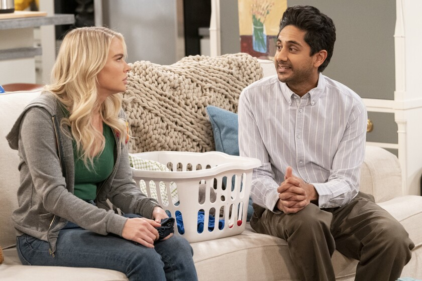 "Kelli Goss and Adhir Kalyan sit on a couch in ""United States of Al"" on CBS."
